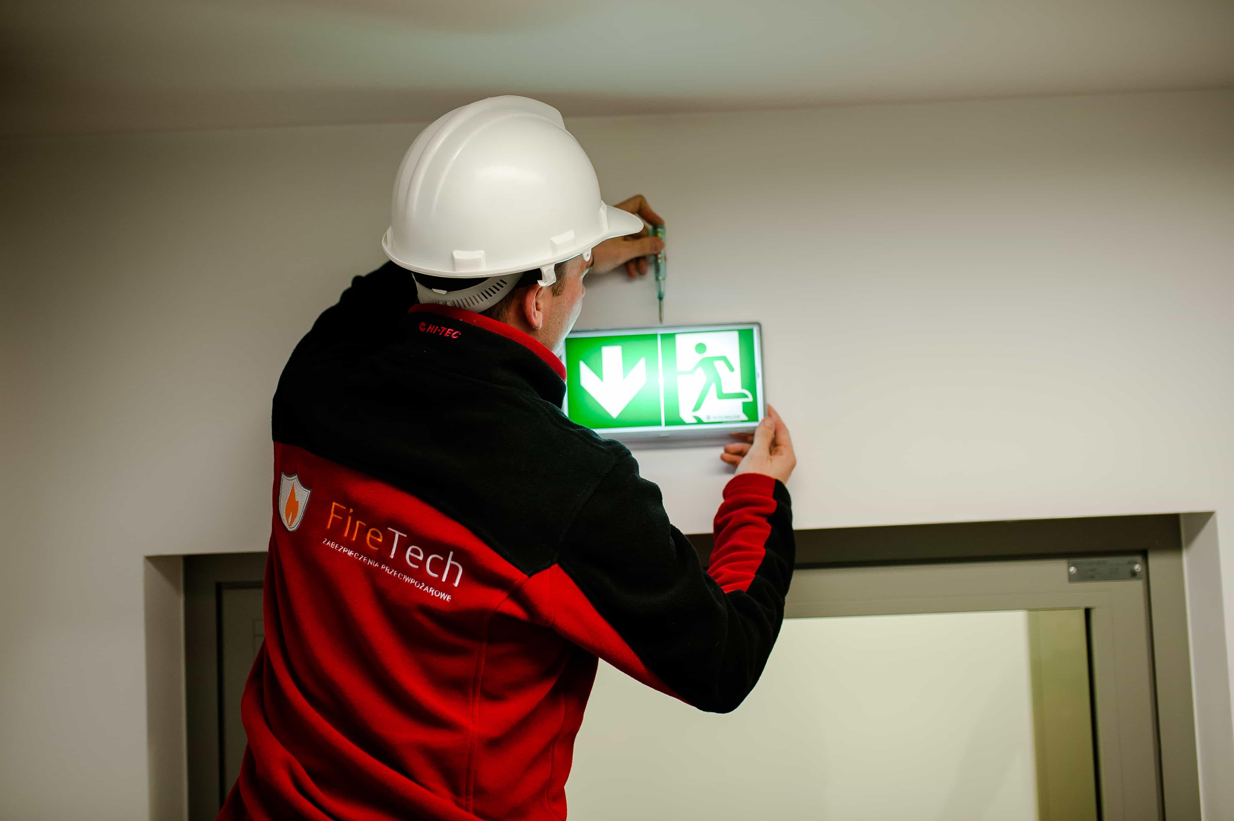Serwisant przy pracy nad oświetleniem awaryjnym